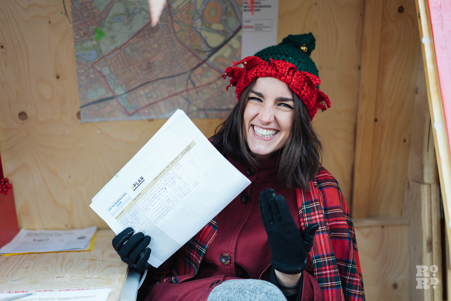 Woman wearing elf hat manning the Neighourhood Forum stand at Roman Road Christmas Fair